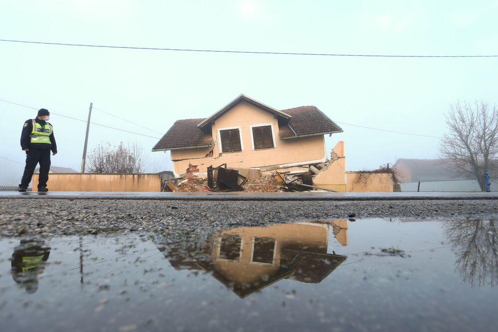 Policista naproti poškozenému domu po zemětřesení v Chorvatsku.