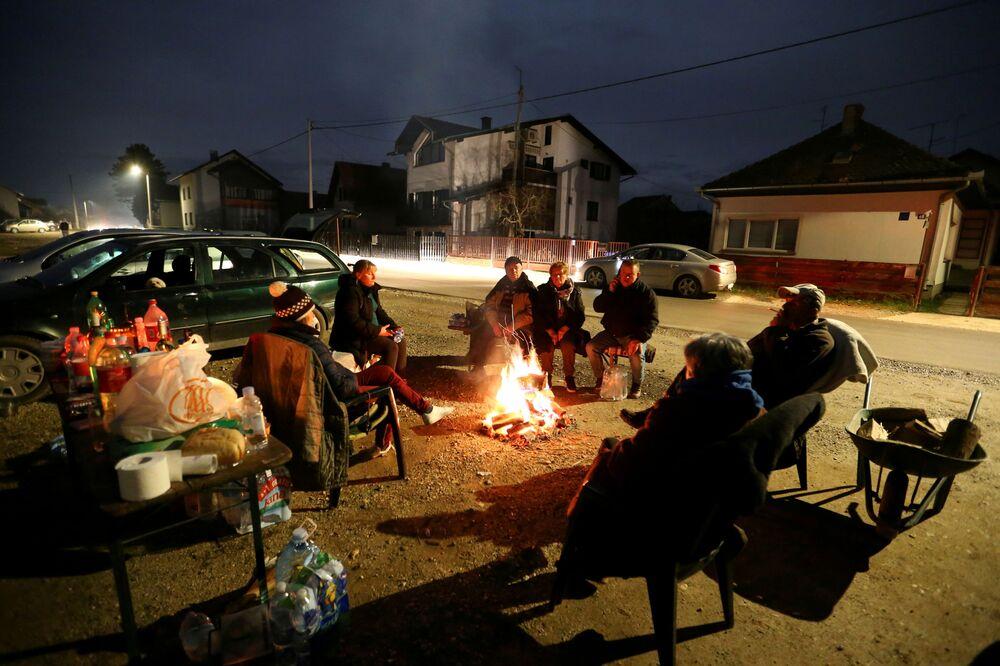 Lidé se zahřívají u ohně po zemětřesení v chorvatském městě Petrinja.