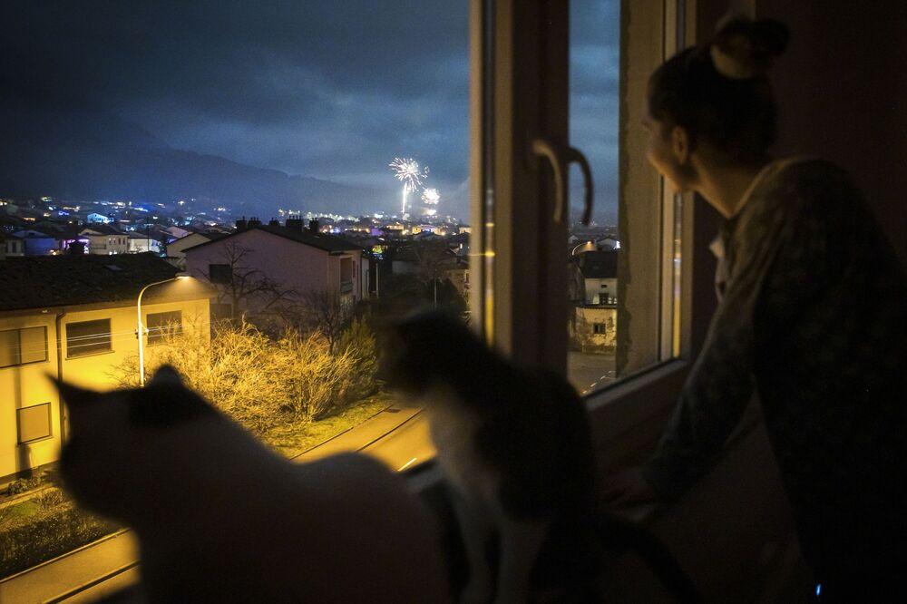 Dívka spolu s kočkamis sleduje novoroční ohňostroj z okna svého domu v Ajdovščině, Slovinsko.