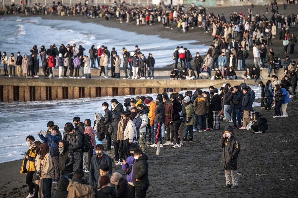 Lidé sledující první východ slunce v novém roce na jižní pláži Chigasaki, v prefektuře Kanagawa, jihozápadně od Tokia.