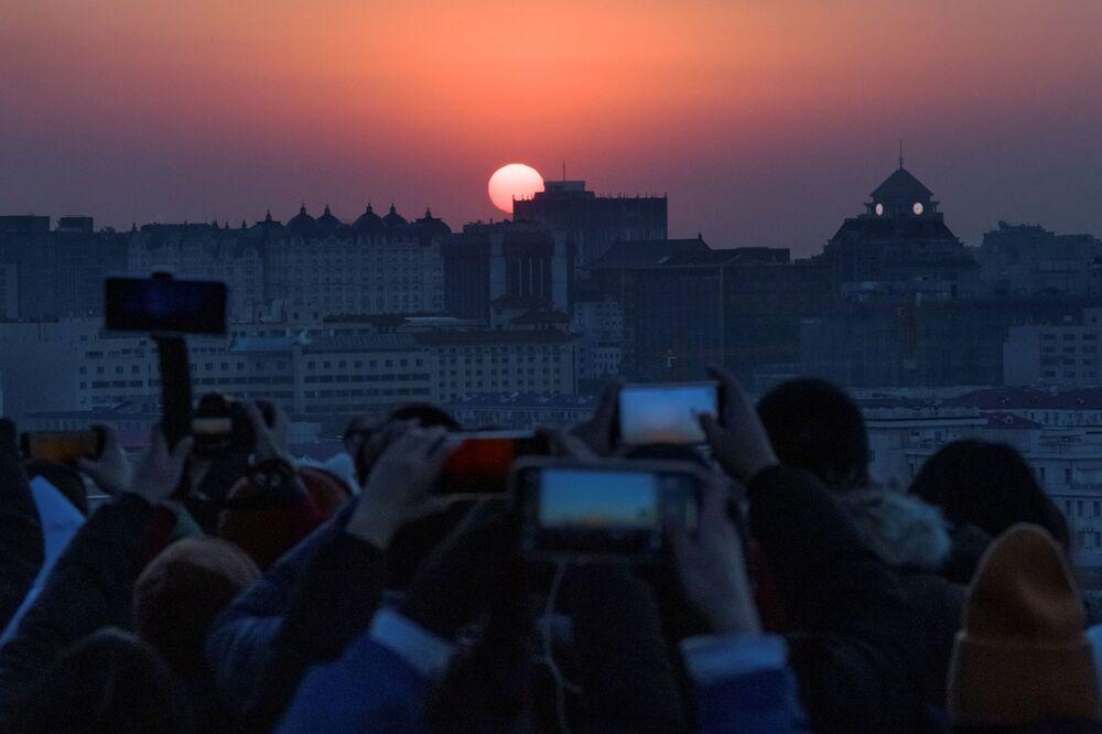 Lidé sledující první východ slunce v novém roce v Beijingu, Čína.