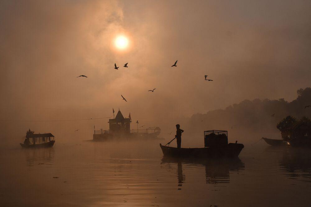 Muž na lodi za mlhy na řece v Indii