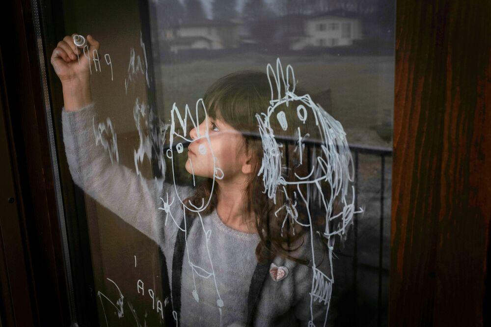 Dívka kreslí na okno na Štědrý den v Itálii