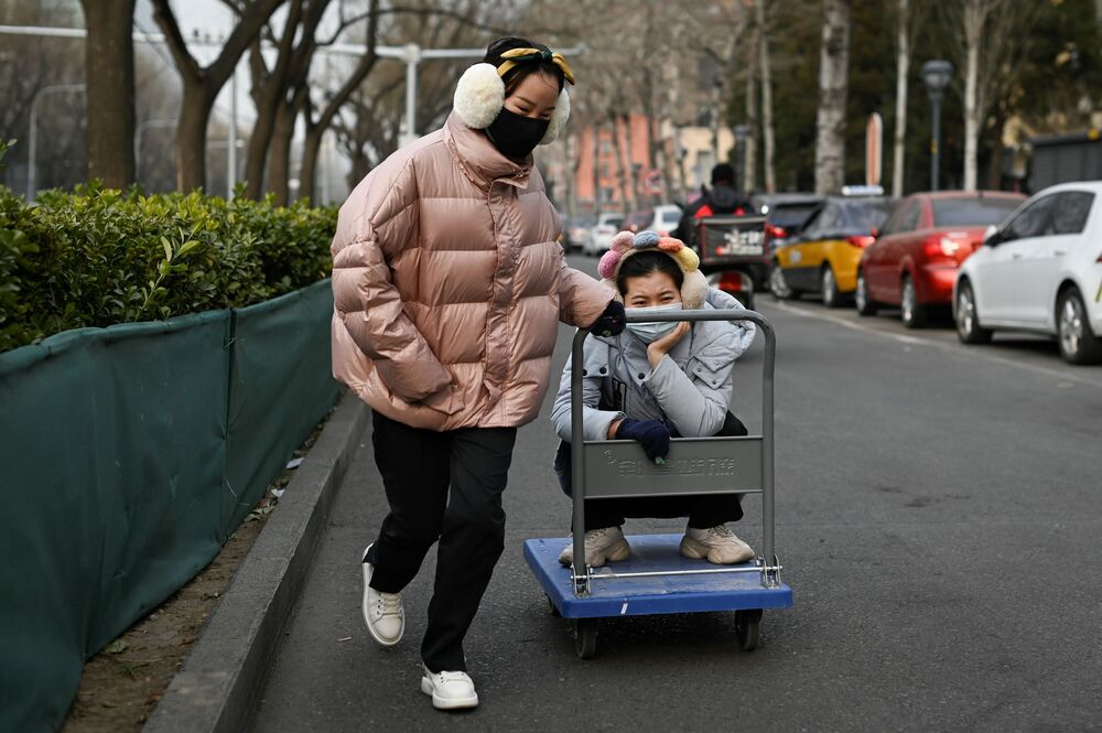 Dívka táhne vozík s přítelkyní v Pekingu