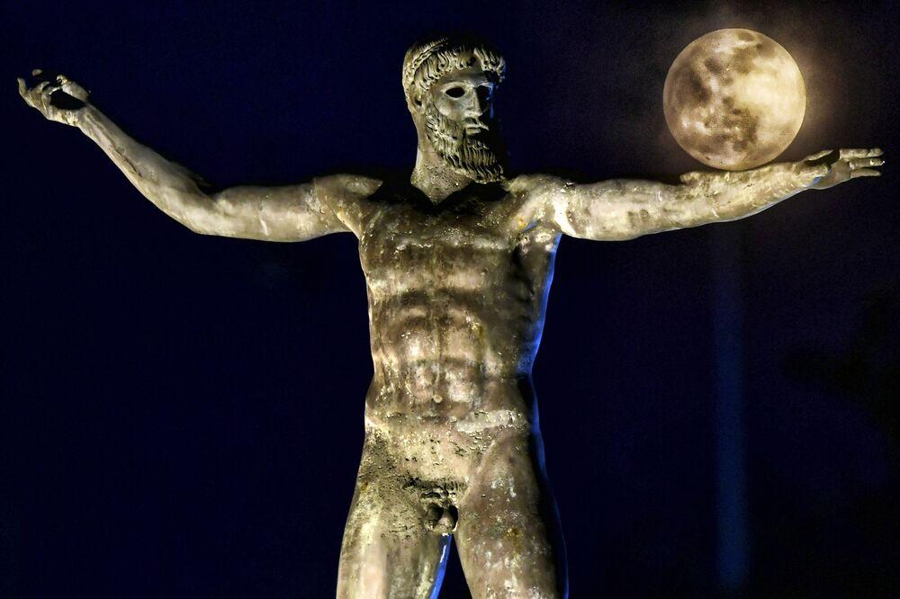Východ Měsíce nad sochou Poseidona v Řecku