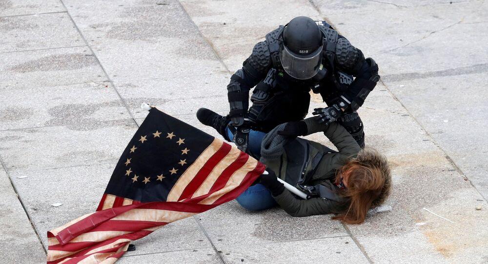 Policista zatýká demonstranta ve Washingtonu