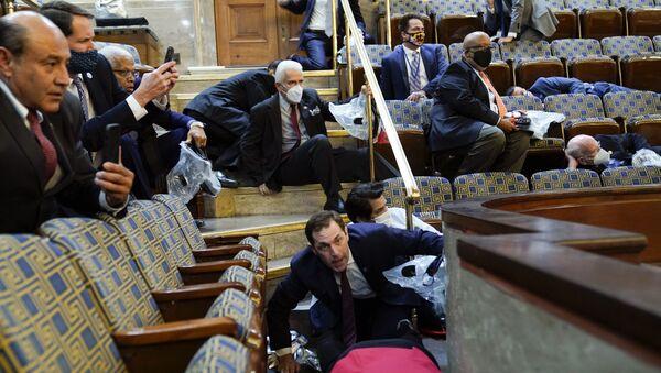 Lidé se ukrývají v Kapitolu, když se demonstranti ve středu pokoušejí proniknout do sněmovny v americkém hlavním městě - Sputnik Česká republika