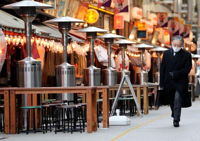 Kolemjdoucí prochází kolem uzavřených restaurací v Tokiu