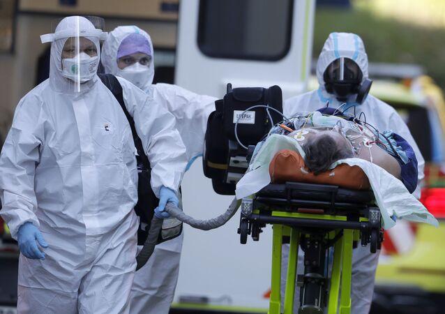 Zdravotníci převážejí pacienta covidem-19 do Motolské nemocnice