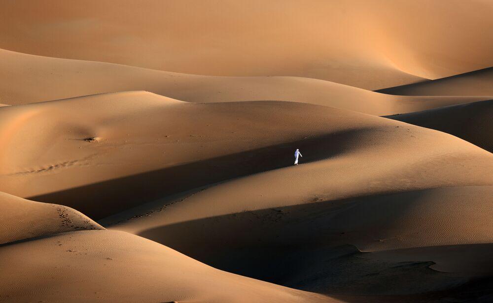 Člověk v písečných dunách ve Spojených arabských emirátech