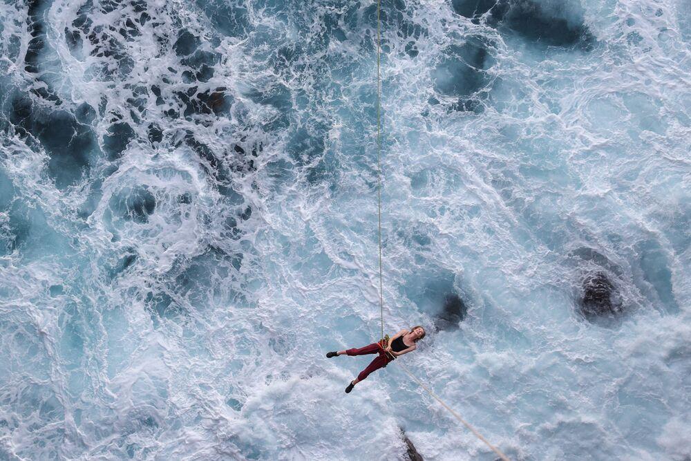 Dívka visí nad oceánem na laně