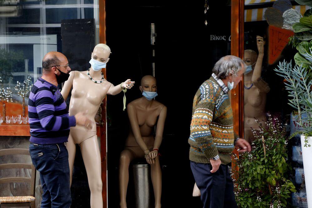 Majitel obchodu nese figurínu v roušce. Nikósie, Kypr