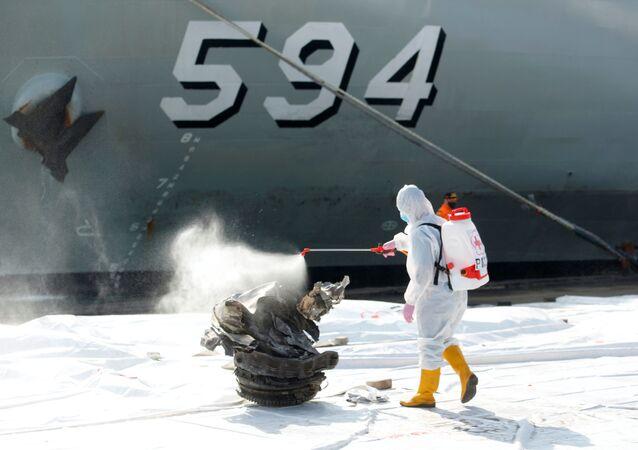 Zaměstnanec Červeného kříže nastříká dezinfekční prostředek na fragment turbíny letadla Sriwijaya Air, které se zřítilo v Jávském moři