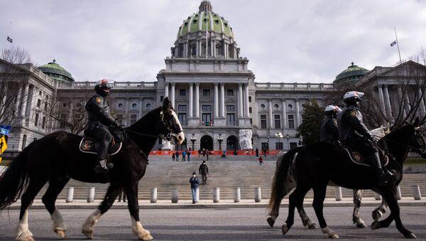 Policisté hlídkují nedaleko budovy Kapitolu státu Pensylvánie v Harrisburu. - Sputnik Česká republika