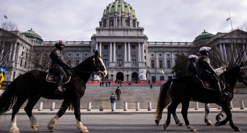 Policisté hlídkují nedaleko budovy Kapitolu státu Pensylvánie v Harrisburu.