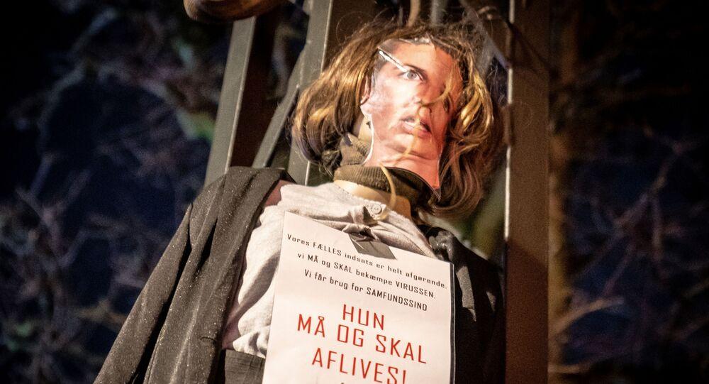 Protestující během násilných protestů proti lockdownu spálili figurínu premiérky. Kodaň, Dánsko