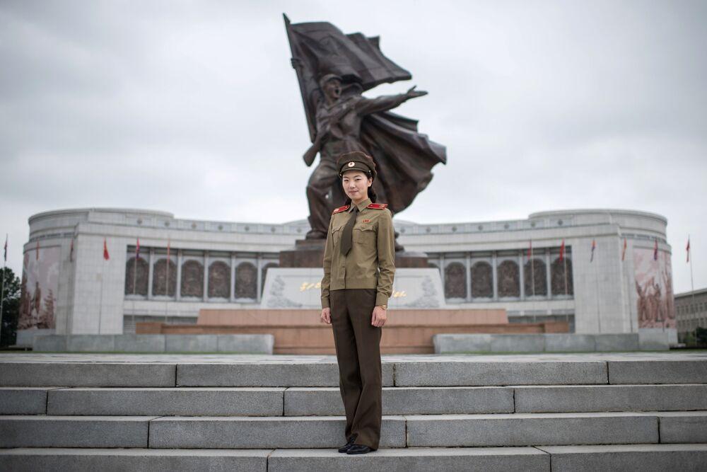 Kapitán korejské lidové armády Choi Un-Čong pózuje před Vojenským muzeem v Pchjongjangu