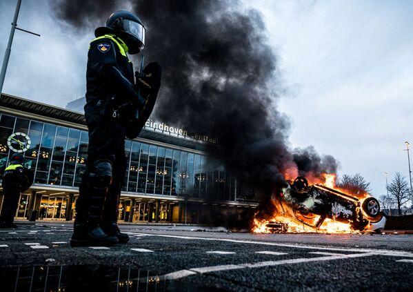 Hořící auto před železniční stanicí v nizozemském Eindhovenu po demonstraci proti vládním opatřením.  - Sputnik Česká republika