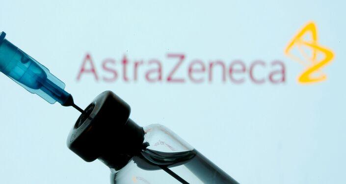 Injekční lahvička a stříkačka před zobrazeným logem AstraZeneca
