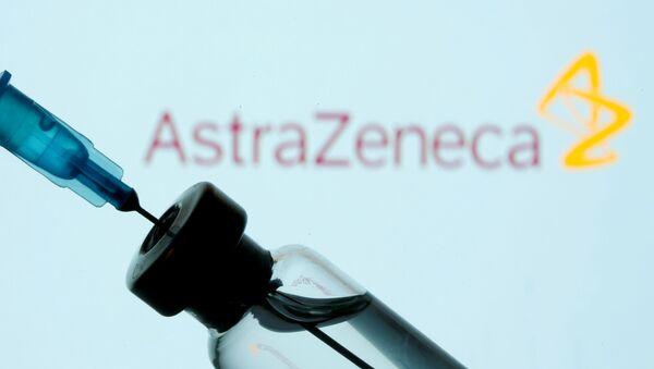 Injekční lahvička a stříkačka před zobrazeným logem AstraZeneca - Sputnik Česká republika