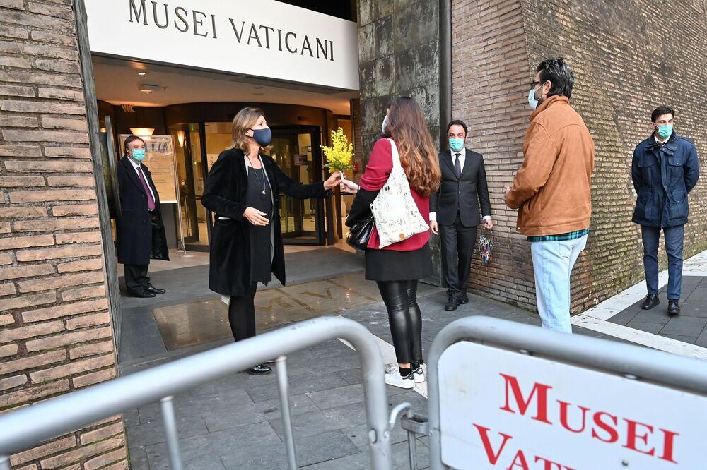První návštěvníci dostávají květiny od ředitelky Vatikánského muzea Barbary Jattaové