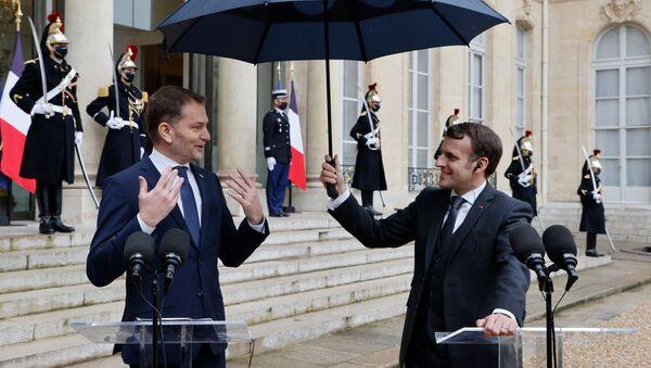 Emmanuel Macron drží deštník Igoru Matovičovi - Sputnik Česká republika