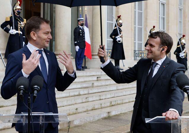 Emmanuel Macron drží deštník Igoru Matovičovi