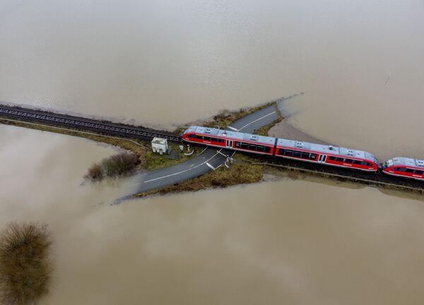 Vlak jede po železnici v zatopené oblasti v Německu - Sputnik Česká republika