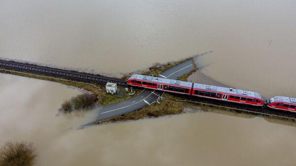 Поезд проезжает по железной дороге на затопленной местности в Германии  - Sputnik Česká republika