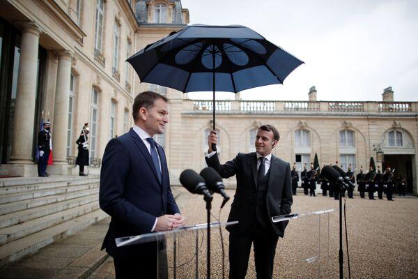 Francouzský prezident Emmanuel Macron drží deštník vedle slovenského premiéra Igora Matoviče během společného prohlášení v Elysejském paláci v Paříži. - Sputnik Česká republika