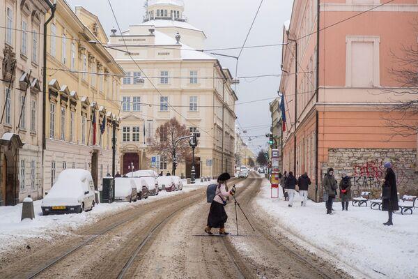 Žena na lyžích přechází ulici v Praze. - Sputnik Česká republika