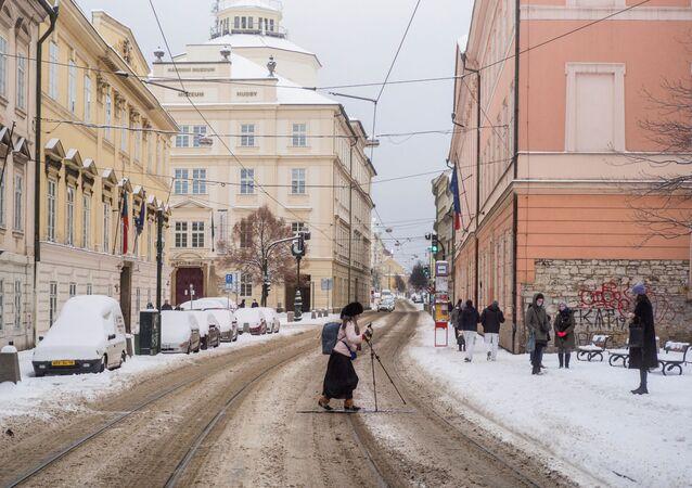 Žena na lyžích přechází silnici v Praze
