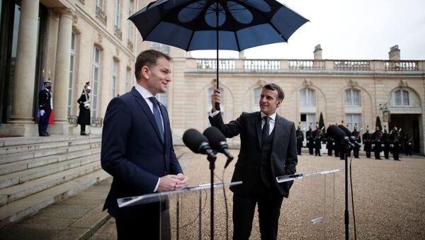 Francouzský prezident Emmanuel Macron drží deštník vedle slovenského premiéra Igora Matoviče během společného prohlášení v Elysejském paláci v Paříži - Sputnik Česká republika