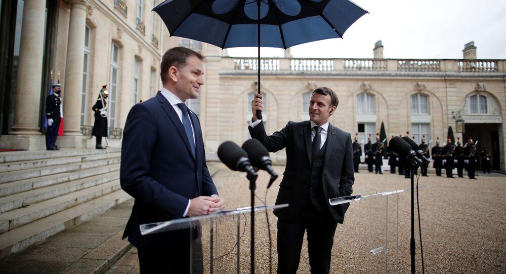 Francouzský prezident Emmanuel Macron drží deštník vedle slovenského premiéra Igora Matoviče během společného prohlášení v Elysejském paláci v Paříži