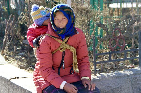 Žena s dítětem na jedné z ulic města Lhasa v Tibetu. - Sputnik Česká republika