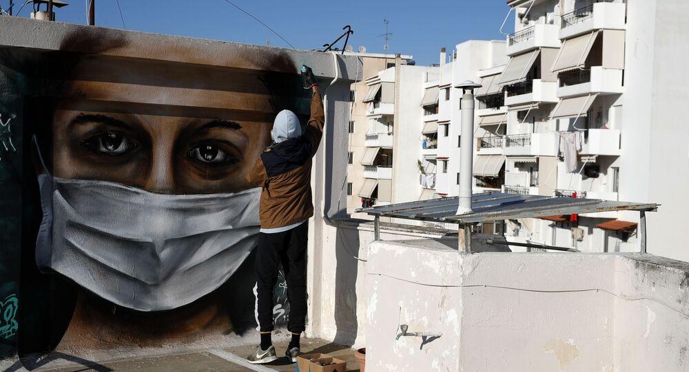Řecký umělec S.F. maluje graffiti na téma koronaviru v Aténách
