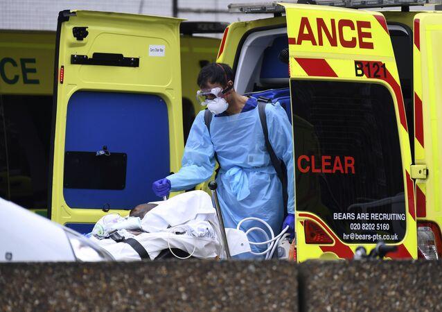 Britští zdravotníci dopravují pacienta s covidem-19 do nemocnice