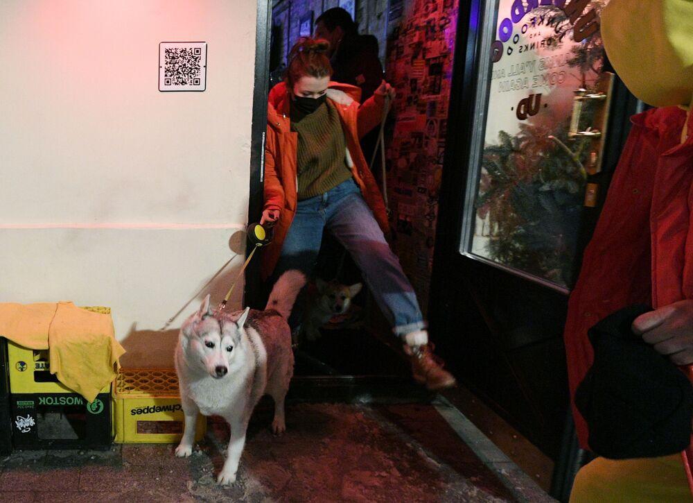 Návštěvník se svým mazlíčkem u vchodu do baru Underdog v Moskvě