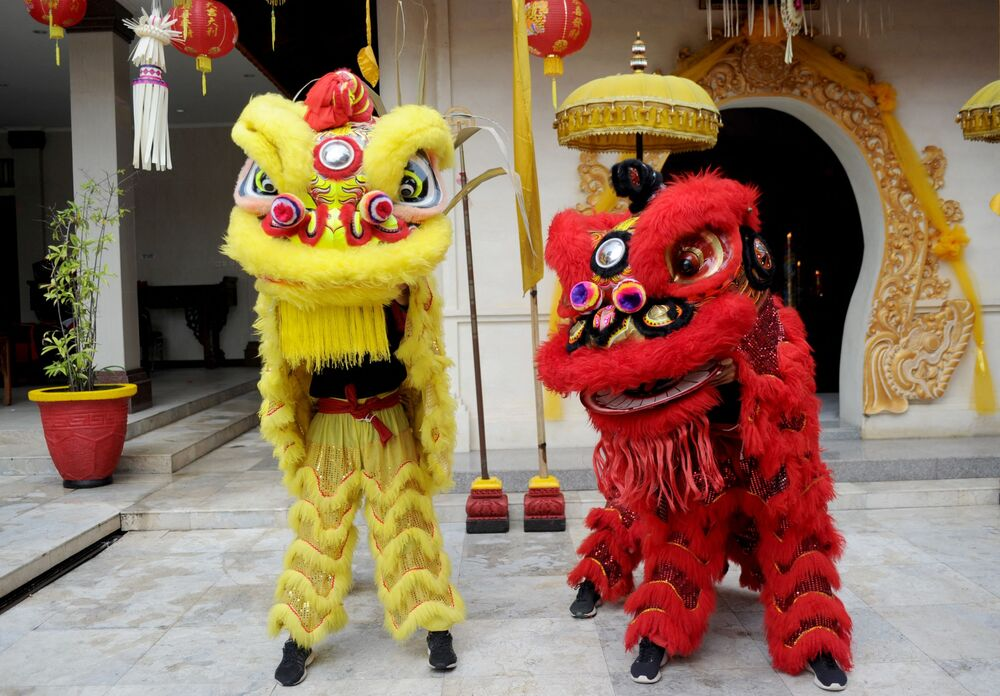 Lidé v kostýmech lvů v čínském chrámu první den lunárního nového roku v Kutě na Bali