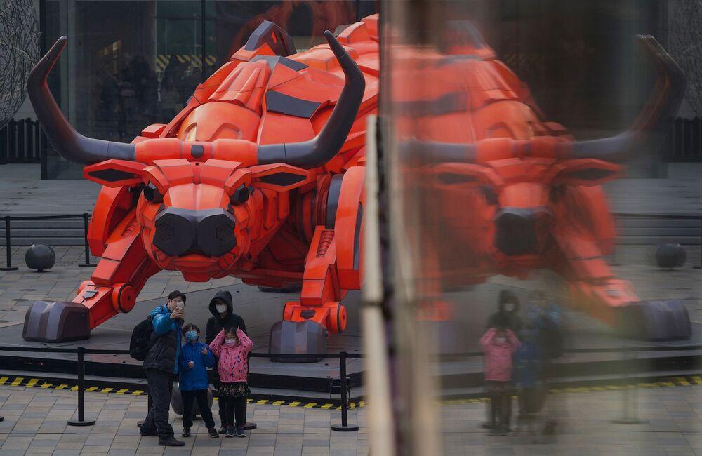 Rodina se fotí před sochou buvola v nákupním středisku v Pekingu