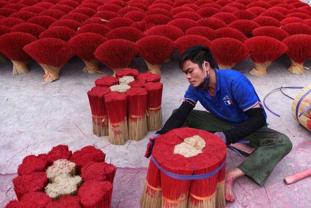 Muž, který balí aromatické tyčinky poblíž Hanoje ve Vietnamu