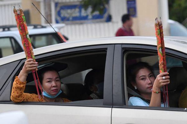 Ženy s aromatickými tyčinkami v autě během oslav lunárního nového roku v Ta Khmau, Kambodža.  - Sputnik Česká republika