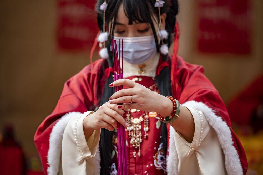 Žena v tradičním oblečení během modlitby v chrámu, Japonsko