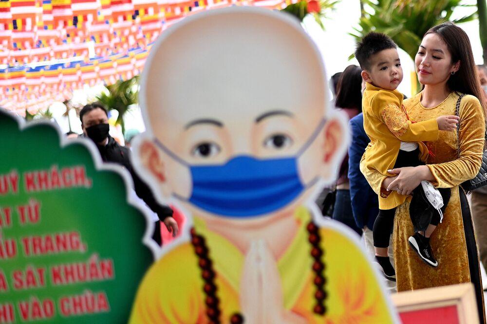Dívka s dítětem v pagodě Chan Kuok v Hanoji, Vietnam