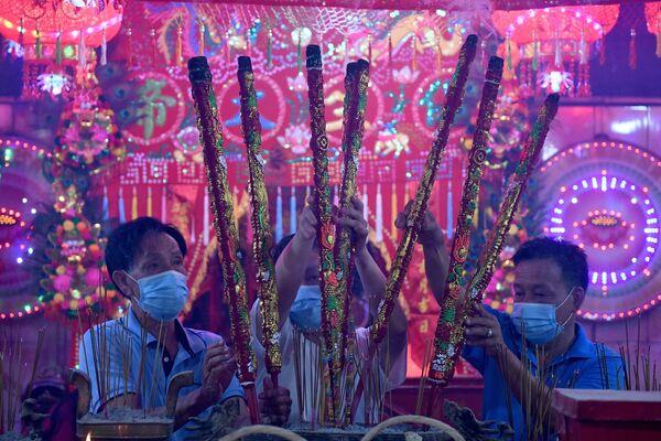 Věřící s aromatickými tyčinkami v chrámu v Ta Khmau, Kambodža.  - Sputnik Česká republika
