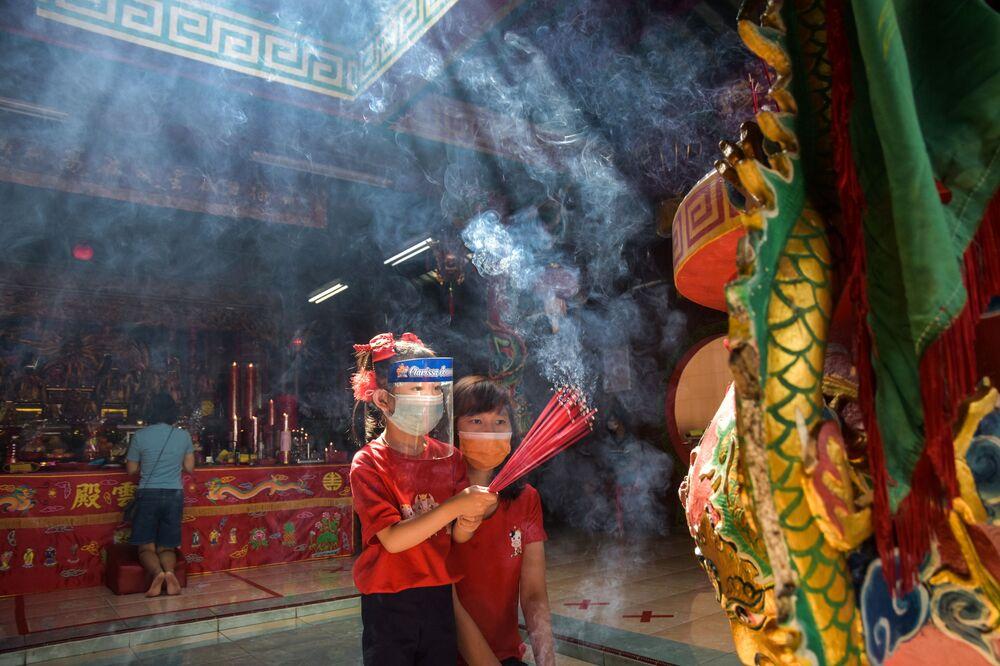Dívky nosící ochranné masky s aromatickými tyčinkami během oslav lunárního nového roku v jednom z indonéských chrámů