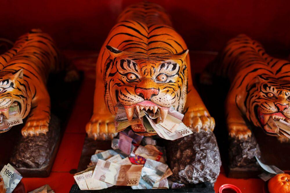 Bankovky u soch tygrů v chrámu Dharma Bhakti během oslav lunárního nového roku v Jakartě, Indonésie