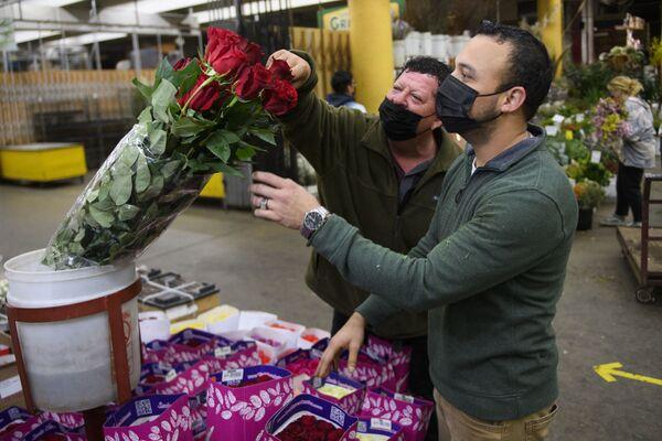 Obchodník pomáhá vybírat kytici před Valentýnem na květinovém trhu v Los Angeles v Kalifornii. - Sputnik Česká republika