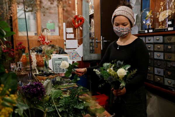Květinářka v ochranné roušce sbírá kytici v květinářství před Valentýnem v Paříži, Francie.  - Sputnik Česká republika