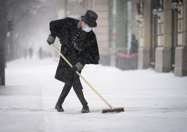 Zaměstnanec hotelu Adlon čistí chodník od sněhu na Pařížském náměstí v Berlíně.  - Sputnik Česká republika